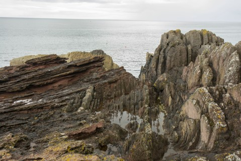 "The ""Classic"" view of Siccar Point with the angular unconformity  between the Old Red Sandstone (dipping gently to the left) and the underlying Devonian turbidites (vertical beds at right). CH Jones July 2015."